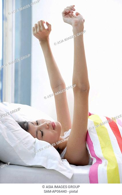 Young woman lying on bed, hands outstretched