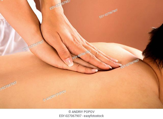 Close-up Of A Man Receiving Back Massage From Therapist In Spa