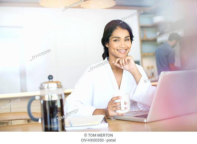 Portrait smiling woman in bathrobe drinking coffee at laptop