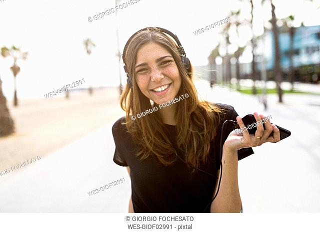 Portrait of happy young woman on boardwalk listening to music