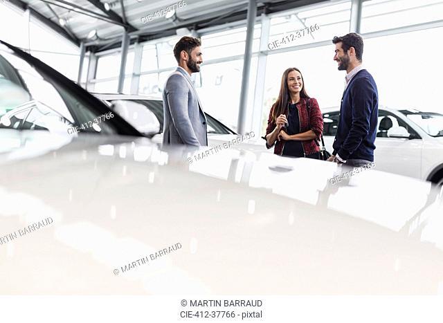 Car salesman talking to couple customers in car dealership showroom