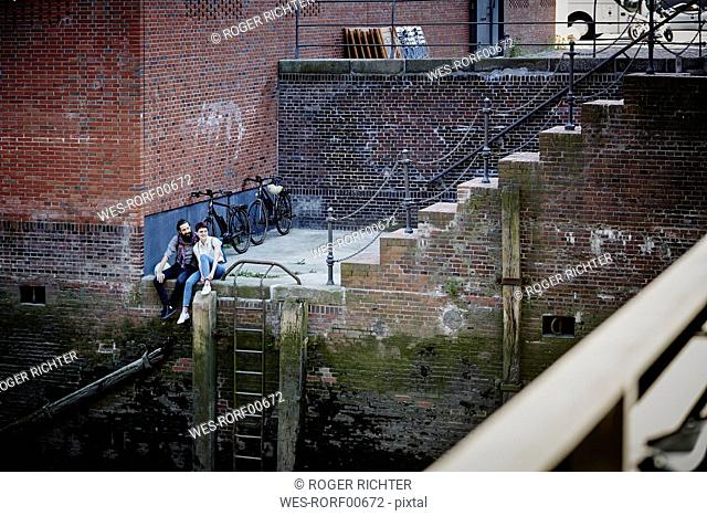 Germany, Hamburg, couple with electric bicycles relaxing at Old Warehouse District