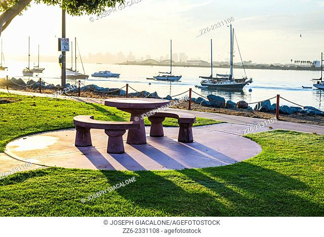 View of a public table and benches during sunrise. Shelter Island Shoreline Park, San Diego, California, United States