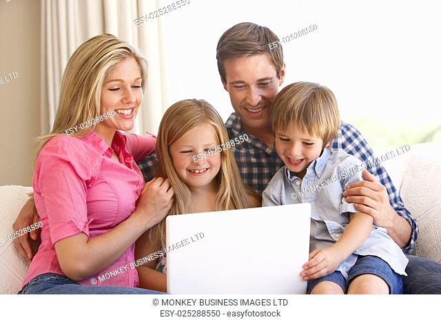 Family Using Laptop On Sofa At Home