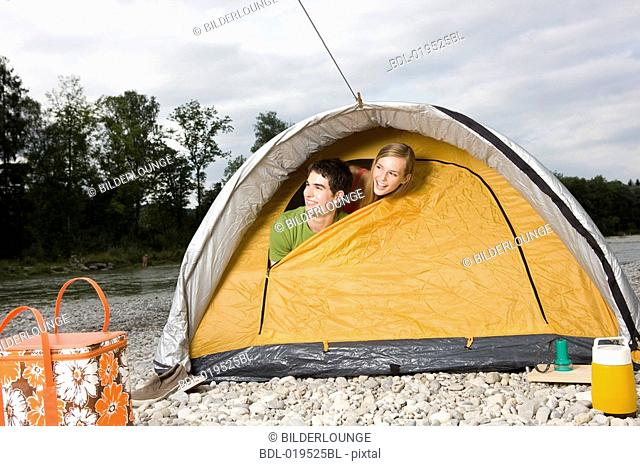young couple peeking through tent in the morning