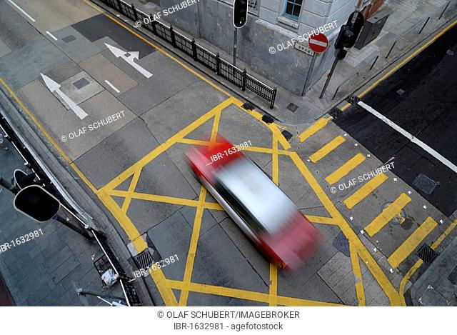 Taxi speeding across an intersection in Soho district, Central district, Hong Kong, China, Asia