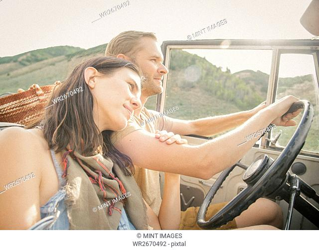 A couple on a road trip in the mountains side by side in a jeep