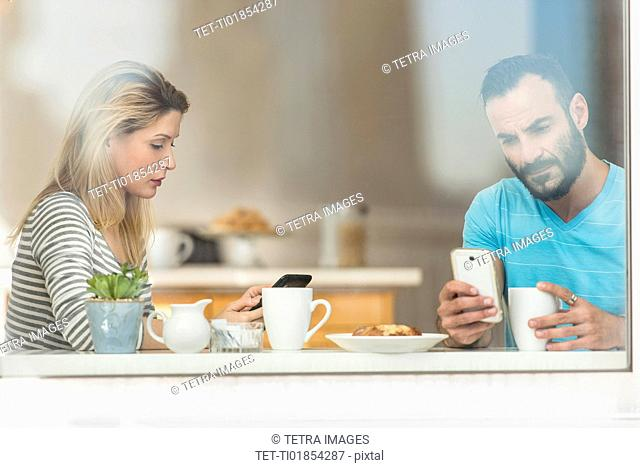 Woman and man using telephones