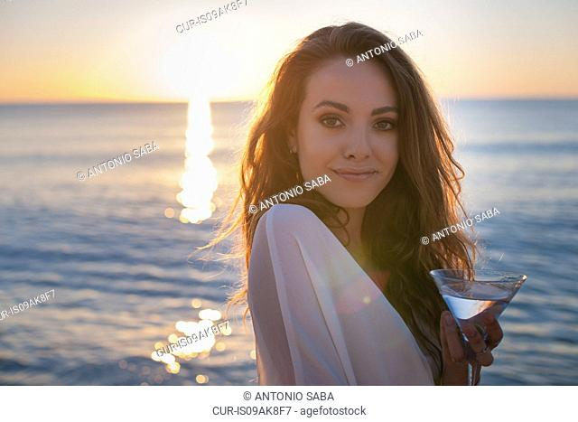 Portrait of young woman on beach with cocktail at sunset, Castiadas, Sardinia, Italy