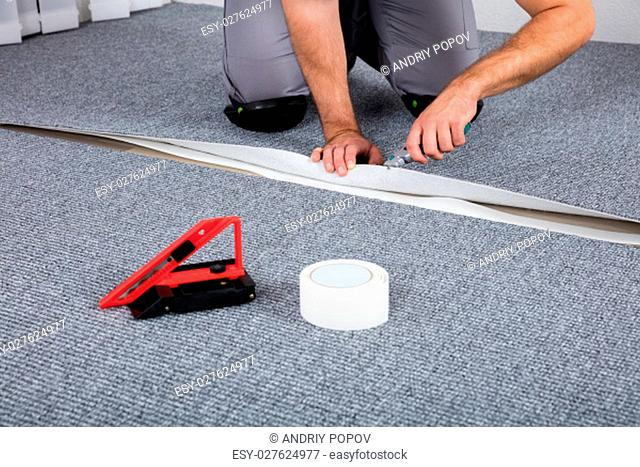 Close-up Of Person's Hand Lying Carpet Using Carpenter Tools