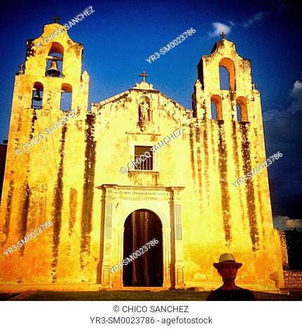 A woman stands in front of the church of Mani, Yucatan, Mexico