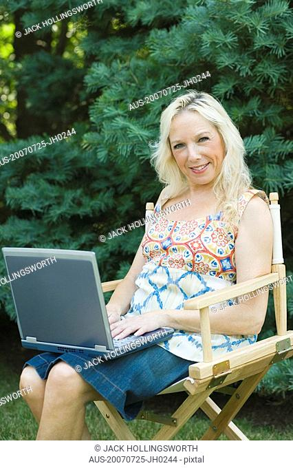 Mature woman sitting in an armchair and using a laptop
