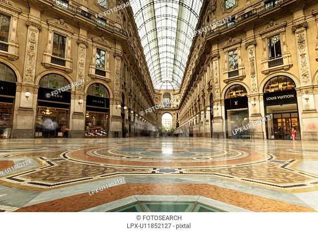 Gallerica Vittorio Emanuele: detail view of central mall area , people shopping, glass and cast iron arched roof with stone carving decoration, Milan Italy