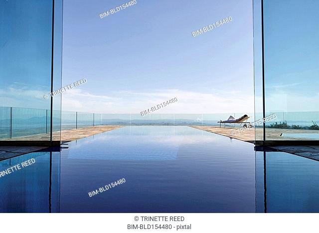 Woman relaxing near infinity pool overlooking scenic view