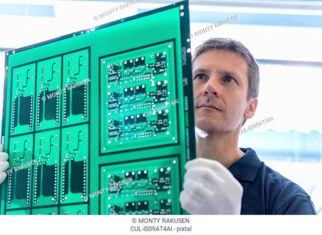 Worker inspecting circuit board during manufacture in circuit board factory