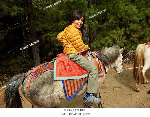 Mixed Race boy riding horse