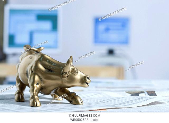Bull figurine on newspaper, background up-up