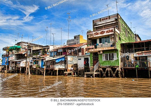 Mekong Delta life on water at river houses slums fishing homesof wood below Saigon Vietnam