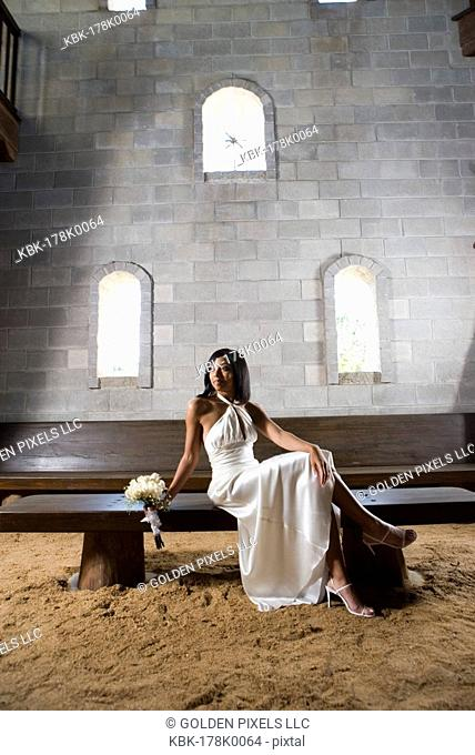 Portrait of a young bride in a white gown sitting on a bench inside a medieval castle
