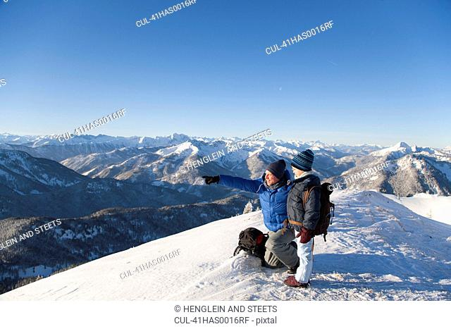 Father and son surveying snowy landscape