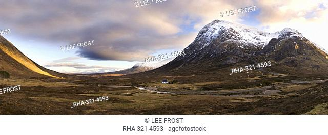 Winter panoramic view of Rannoch Moor showing lone whitewashed cottage on the bank of a river, dwarfed by snow-covered mountains, Rannoch Moor