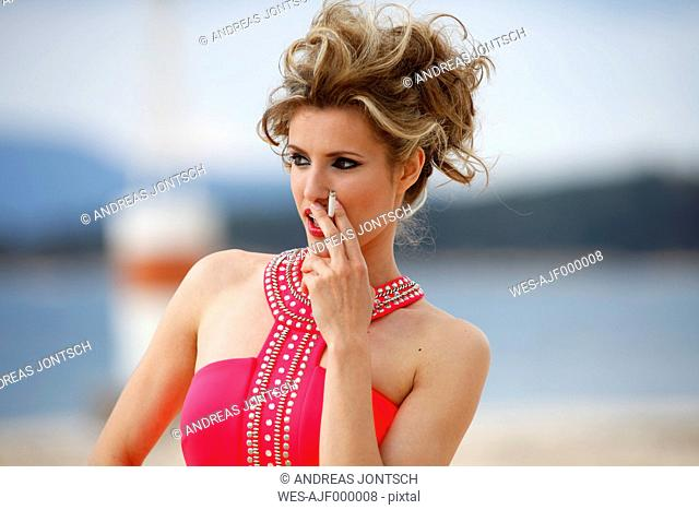 Greece, Young woman smoking cigarette at sea, close up