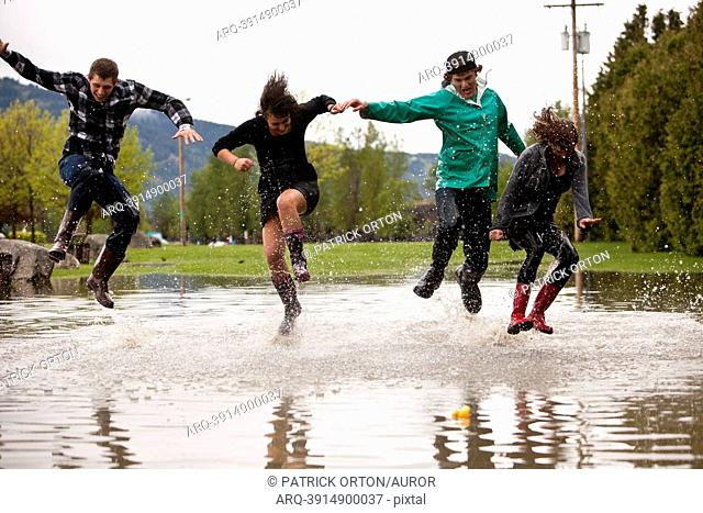 Young adults jump and splash in a large puddle