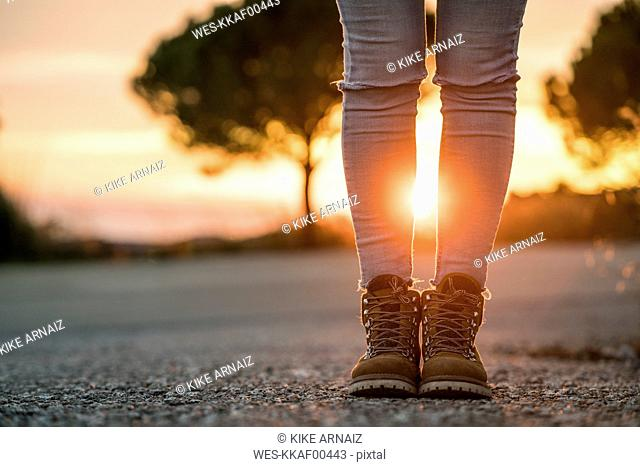 Woman wearing hiking boots standing on a road at sunset