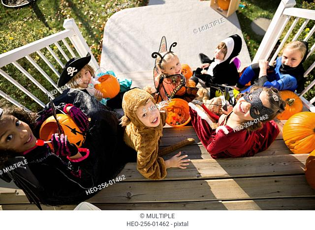 Overhead portrait kids Halloween costumes sitting front stoop