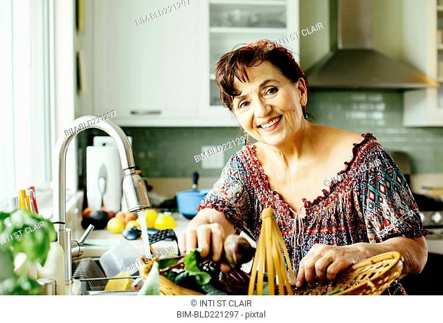 Caucasian woman with produce basket in kitchen