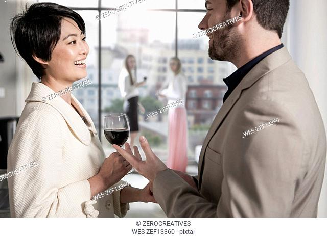 Man and woman with red wine glass socializing in a city apartment