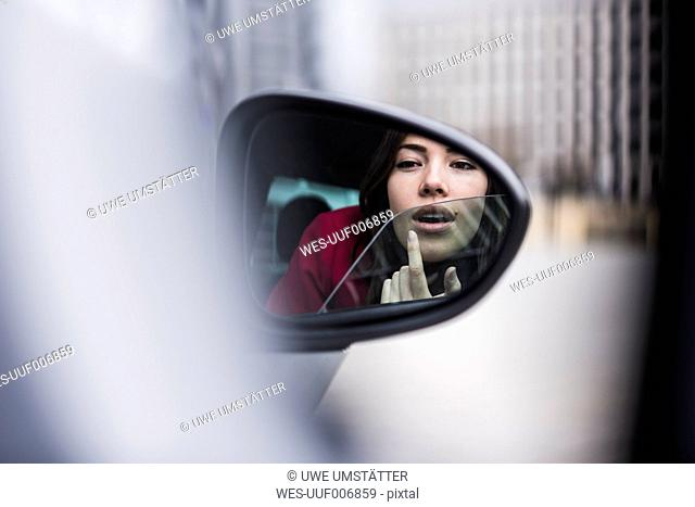 Pretty woman sitting in car applying make up in wing mirror
