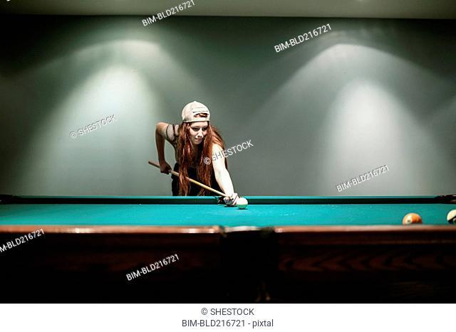 Caucasian teenage girl playing pool