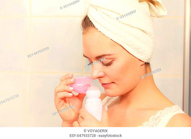 Woman holding stick deodorant in hands. Girl in bathroom towel on head with antiperspirant cosmetics. Daily skin care and hygiene
