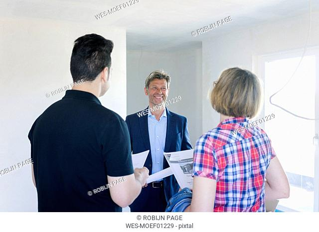 Smiling man in suit talking to couple in unfinished building