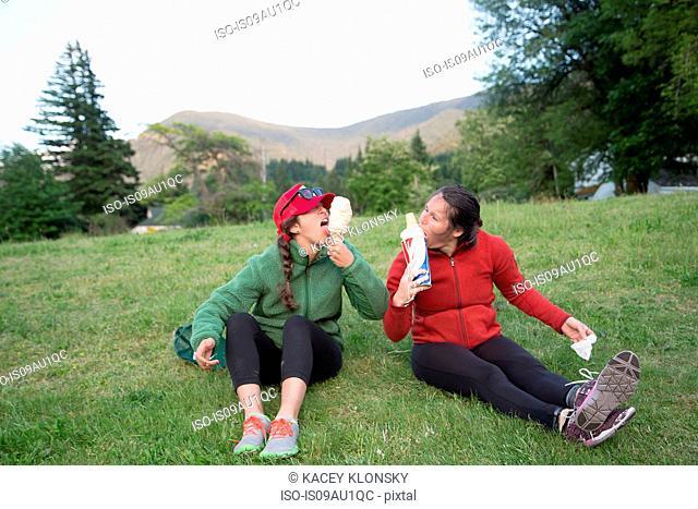 Hikers enjoying ice cream cone on grass, Lake Blanco, Washington, USA