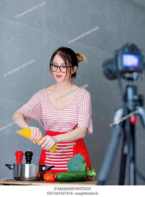 Young redhead woman making cooking video for social network