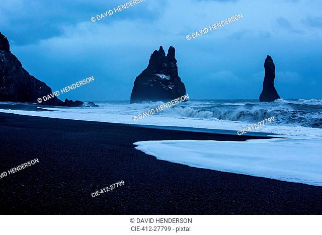 Rock formations and stormy ocean at dusk, Reynisdrangar, Vik, Iceland