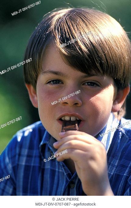 Young boy eating chocolate