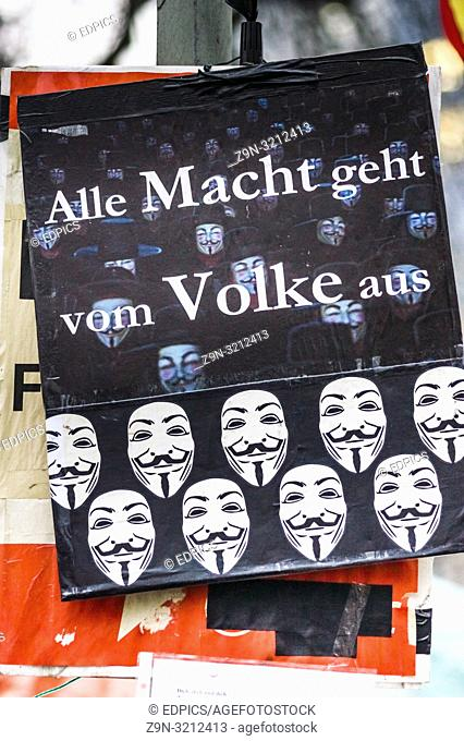 """poster showing various guy-fawkwes-masks and a text that reads: """"""""all power derives from the people"""""""", franfurt/main, hesse, germany"""