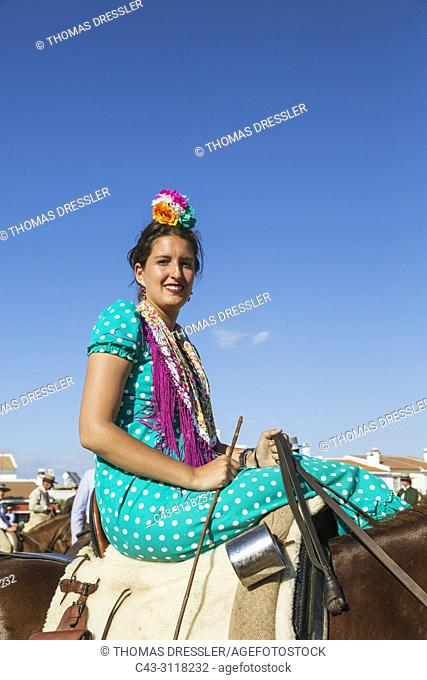 Horsewoman wearing a beautifully coloured gypsy dress during the annual Pentecost pilgrimage of El Rocio. Huelva province, Andalusia, Spain