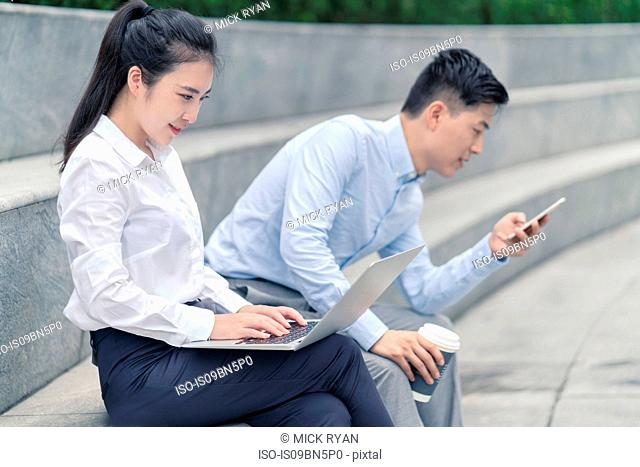 Young businesswoman and man using laptop and looking at smartphone on city seat, Shanghai, China