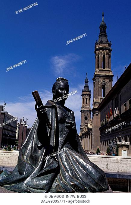 Female figure in 18th century clothes, bronze statue in the monument to Francisco de Goya, 1908, Plaza del Pilar, with the Basilica of Our Lady of the Pillar in...