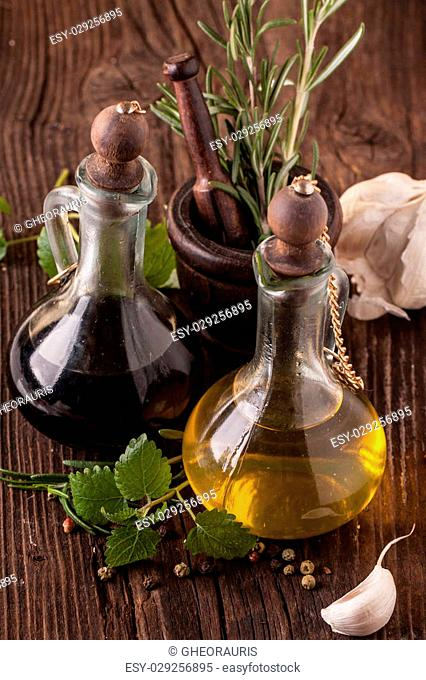 Top view on olive oil and vinegar in vintage bottles on wooden table with garlic, mint and rosemary in wooden mortar