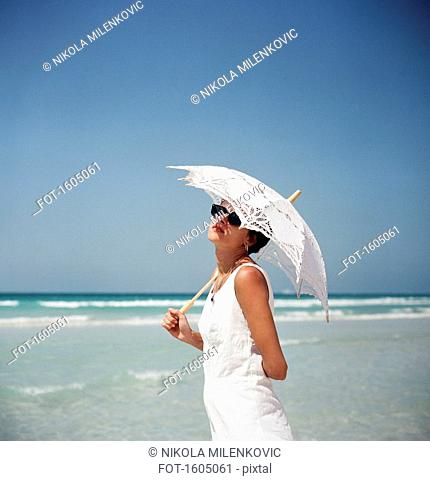 Portrait of a woman holding a parasol and standing on a beach