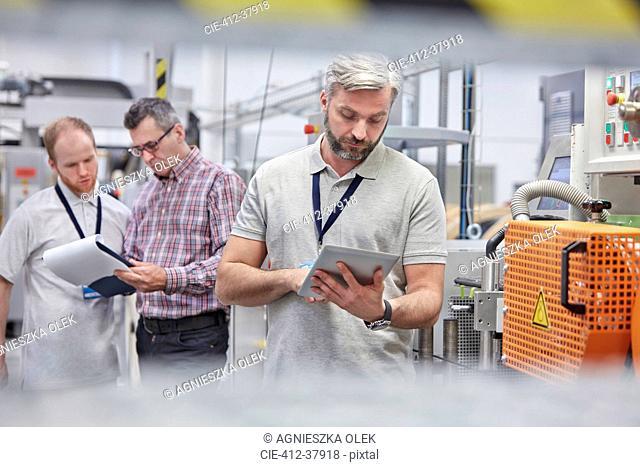 Male supervisor using digital tablet in fiber optics factory