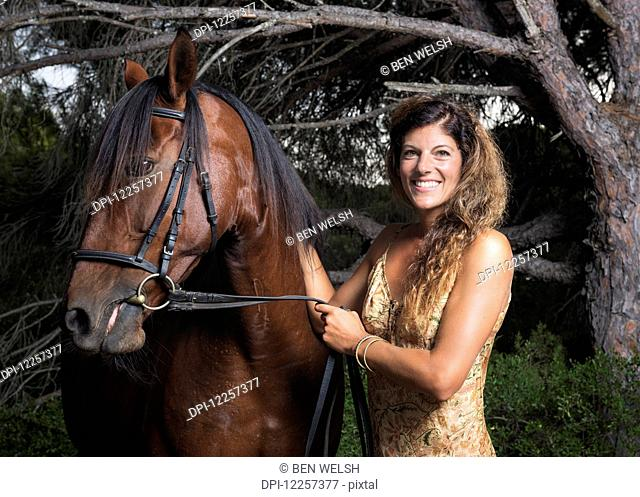 A woman standing with a horse; Tarifa, Cadiz, Andalusia, Spain