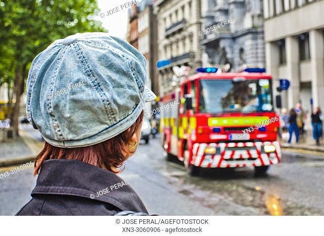 Woman with hat watching the fire truck arrive, Dublin city, province of Leinster, Ireland, Europe