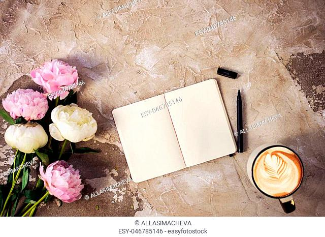 Fresh pink peonies flowers on aged wooden background. Flat lay. Top view with copy space. Cappuccino cup with heart and opened blank note book