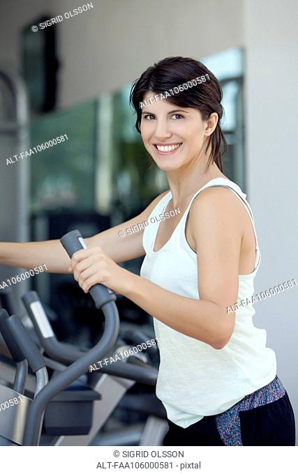 Woman exercising in fitness club, smiling cheerfully